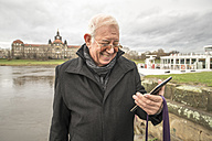 Germany, Dresden, smiling senior man looking at his phablet in front of Elbe River - TAMF000517
