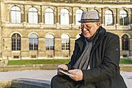 Germany, Dresden, senior man looking at flyers - TAMF000520