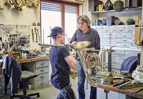 Two instrument makers repairing brass instrument in workshop - DIKF000197