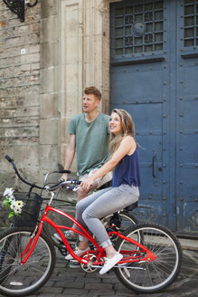 Couple with bicycles in front of an old church - VABF000598