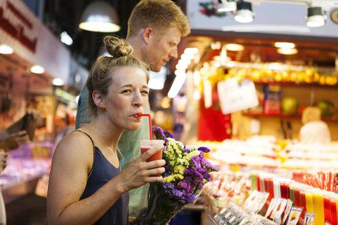 Man drinking smoothie on a street market - VABF000604