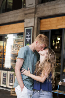 Couple kissing in front of a coffee shop - VABF000607