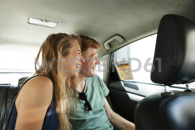 Laughing couple sitting in taxi looking through window - VABF000622