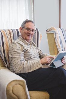 Senior man at home using digital tablet - EPF000112