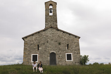 Italy, Udine, two best friends sitting on a meadow in front of a chapel - BOYF000421