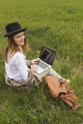 Woman with laptop sitting on a meadow looking at distance - BOYF000424