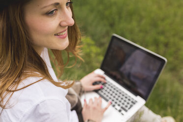 Woman with laptop sitting on a meadow looking at distance - BOYF000427