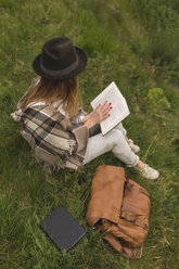 Young woman sitting on a meadow reading a book - BOYF000436
