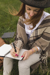 Young woman sitting on a meadow writing down something in her notebook - BOYF000439