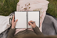 Woman sitting on a meadow writing down something in her notebook, partial view - BOYF000451