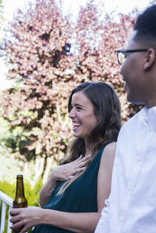 Woman laughing, drinking a bottle of beer during a summer dinner in a garden - ABZF000717
