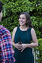 Woman laughing during a conversation with a man drinking a bottle of beer in a garden - ABZF000720
