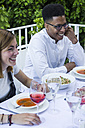 Young man and woman smiling during a summer dinner - ABZF000732