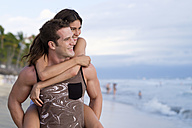Young man giving his girlfriend a piggyback ride on the beach - ABAF002054