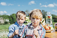 Two boys outdoors drinking from jars - MJF001903