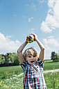Boy outdoors holding glass with jelly beans - MJF001915