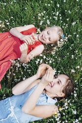 Two happy girls lying in flower meadow - MJF001924