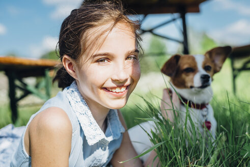 Portrait of smiling girl with dog in meadow - MJF001945