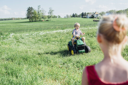 Boy riding toy tractor on field - MJF001960