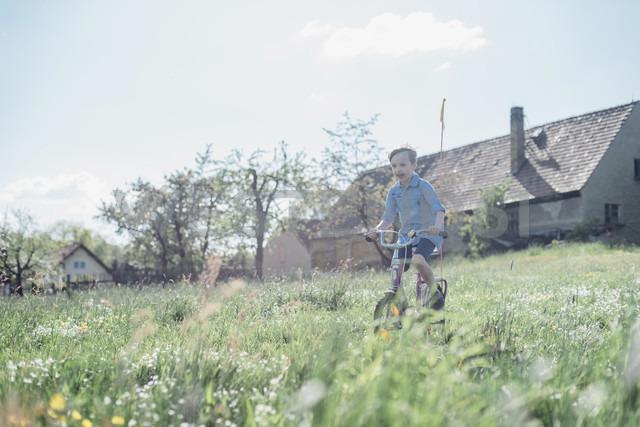 Boy riding bicycle on field - MJF001966 - Jana Mänz/Westend61