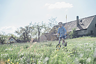 Boy riding bicycle on field - MJF001966