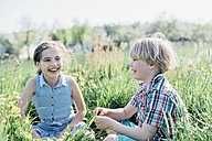 Happy boy and girl sitting in meadow - MJF001969