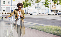 Young woman looking at her smartphone while pushing bicycle - UUF007729
