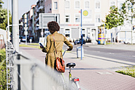 Back view of young woman looking at her smartphone while pushing bicycle - UUF007732