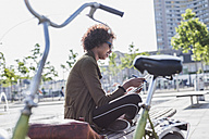 Young woman sitting on a bench with notebook - UUF007738
