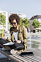 Young woman sitting on a bench with beverage and smartphone reading notes - UUF007741