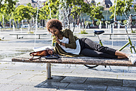 Young woman lying on a bench drinking beverage while looking at her smartphone - UUF007747