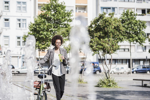 Portrait of smiling woman with bicycle listening music with earphones - UUF007750