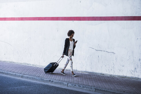 Walking businesswoman with baggage looking at her smartphone - UUF007756