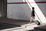 Businesswoman with baggage and smartphone walking down the street - UUF007759