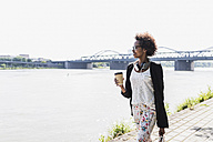 Germany, Mannheim, young businesswoman with coffee to go walking at riverside - UUF007768