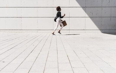 Running businesswoman with smartphone and briefcase - UUF007771
