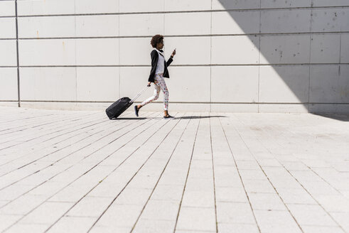 Walking businesswoman with trolley bag looking at her smartphone - UUF007774