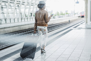 Back view of young woman with smartphone and baggage at platform - UUF007777