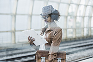 Young woman with briefcase and file reading while waiting at platform - UUF007780