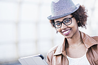 Portrait of smiling young woman wearing hat and glasses - UUF007783