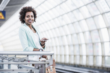 Portrait of young woman with earphones and smartphone waiting at platform - UUF007786