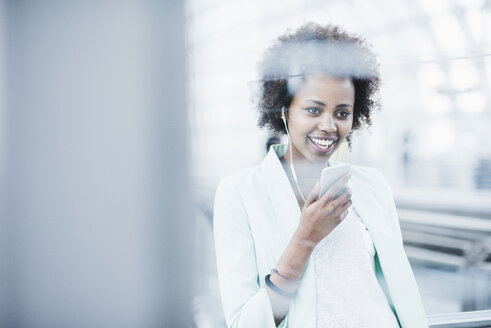 Portrait of smiling young woman with earphones and smartphone at platform - UUF007789
