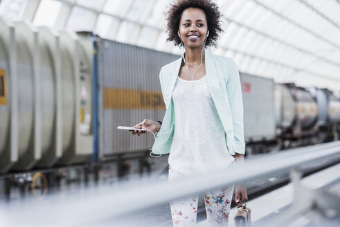 Portrait of smiling young woman with earphones and smartphone at platform - UUF007792
