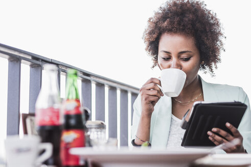 Young woman in a cafe drinking coffee while looking at her digital tablet - UUF007795