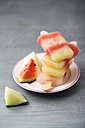 Plate with stack of different homemade melon ice lollies - MYF001593