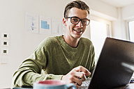 Portrait of smiling man at desk with laptop - UUF007833