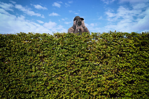 Paparazzi with camera behind hedge - KLRF000392