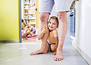 Daughter sitting on floor, holding onto father's leg - HAPF000507