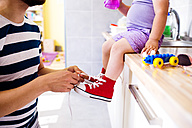 Father putting his daughter shoes on - HAPF000519