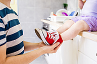 Father putting his daughter shoes on - HAPF000522